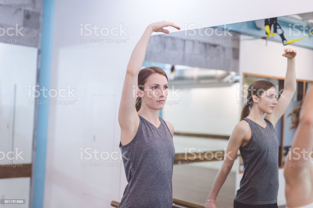 Young woman does barre workout at modern gym stock photo