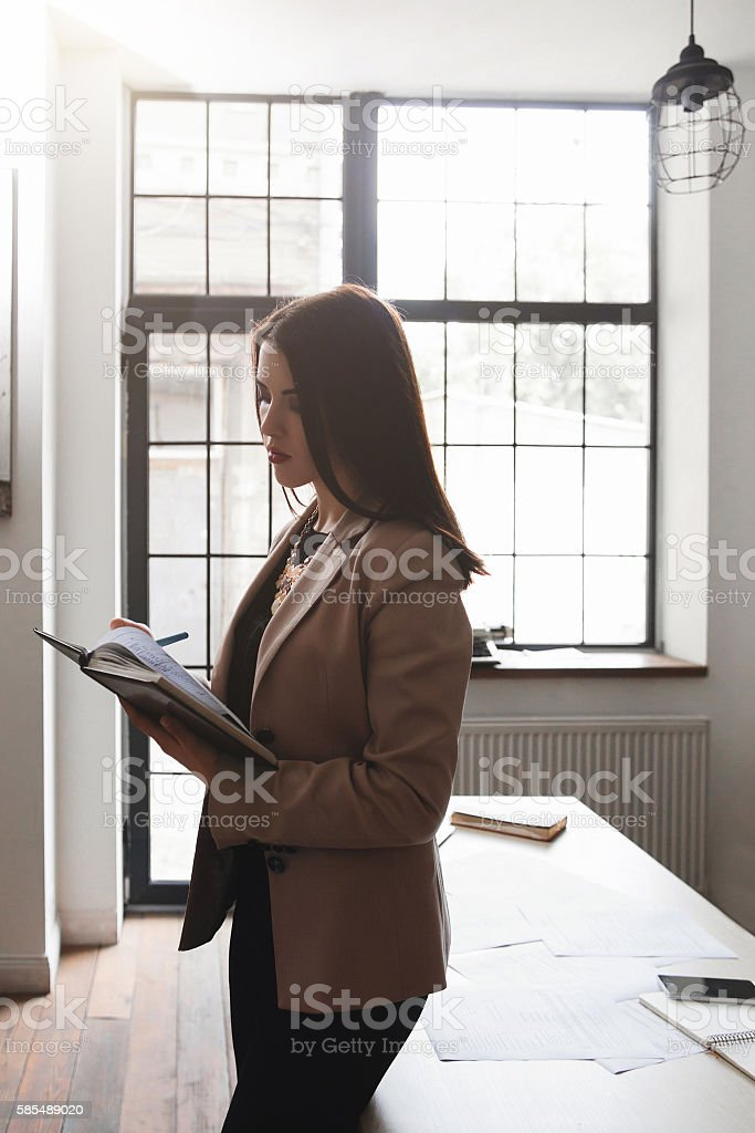 Young woman does inventory of company supplies stock photo