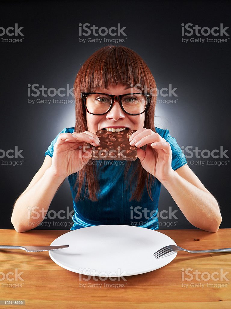 Young woman does not count calories, eating chocolate bar royalty-free stock photo