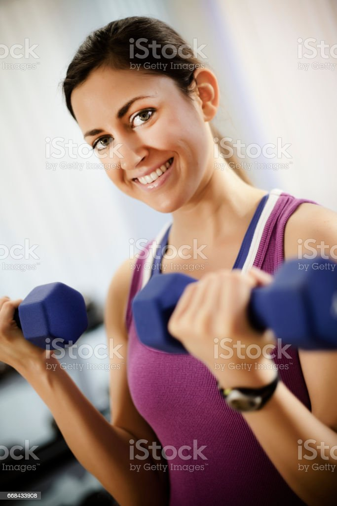 Young Woman Doing Arm Curls With Dumbbells stock photo