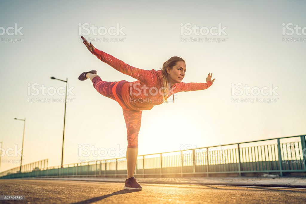 Young woman doing balance exercise at sunset. stock photo