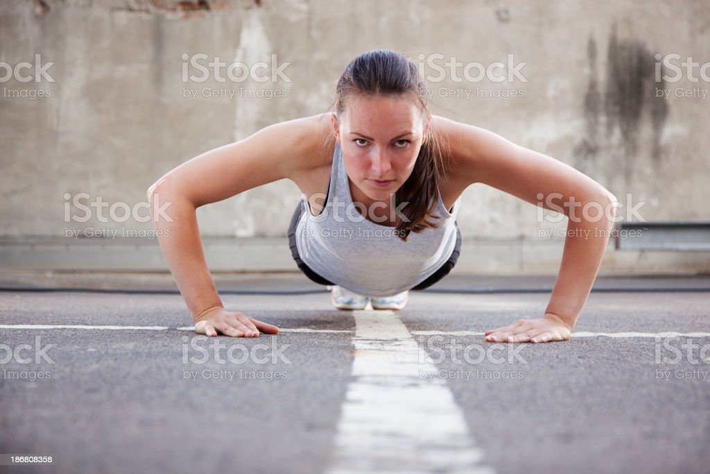 Young woman doing Burpee exercise royalty-free stock photo