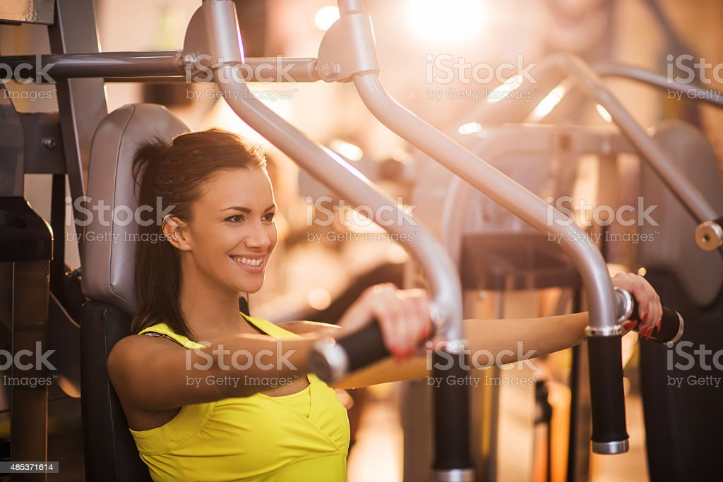 Young woman doing chest exercises on exercise machine at gym. stock photo