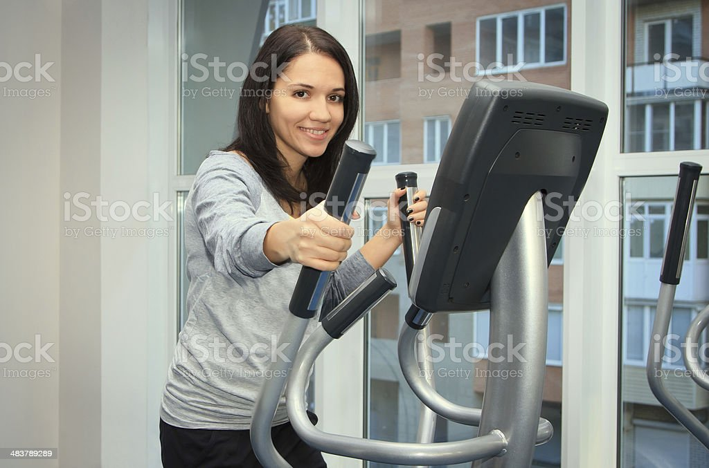 young woman doing exercise on a elliptical trainer stock photo