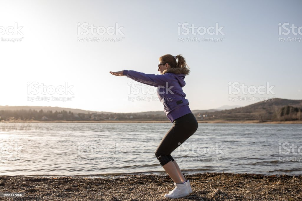 young woman doing exercise on lake shore stock photo