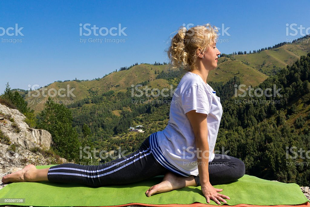 Young woman doing exercises in the mountains stock photo