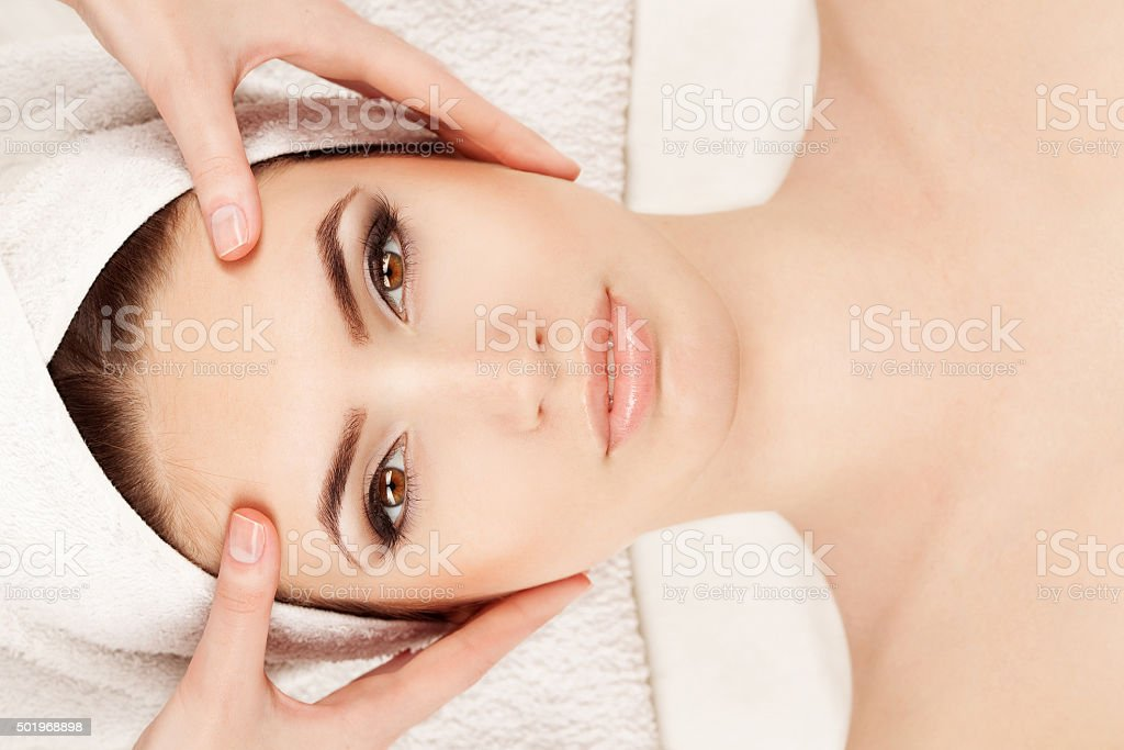 Young woman doing facial massage stock photo