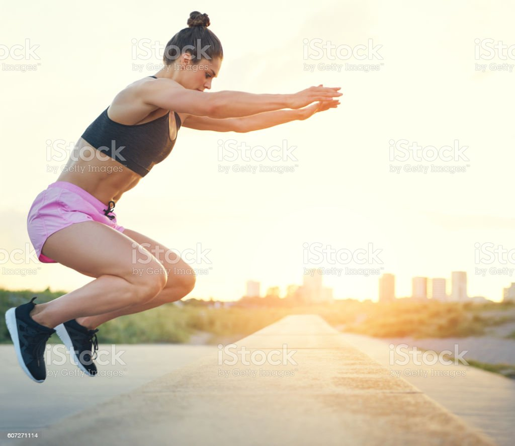 Young woman doing gym exercises outdoors stock photo