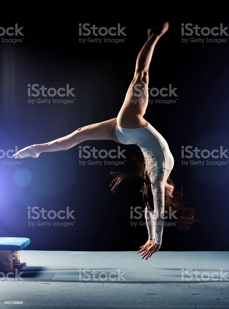 Young woman doing gymnastics jump stock photo