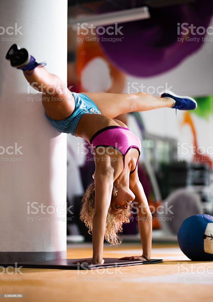 Young woman doing handstand and balancing in a gym. stock photo