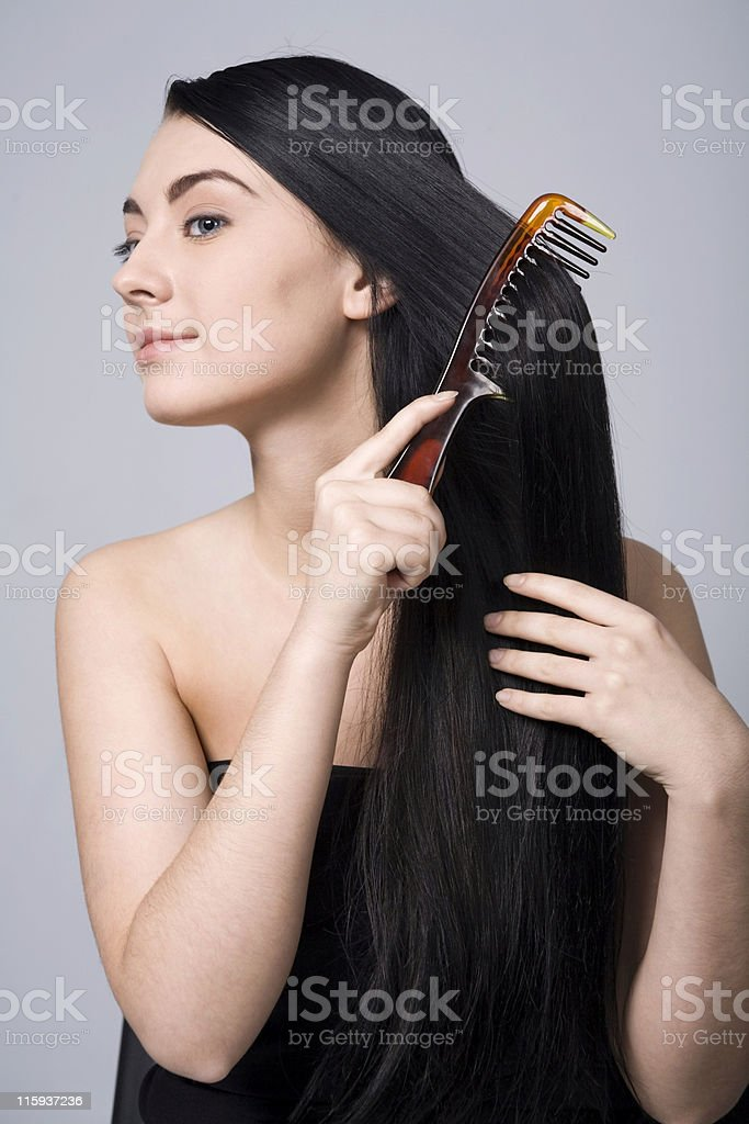 Young woman doing her beautiful dark hair stock photo