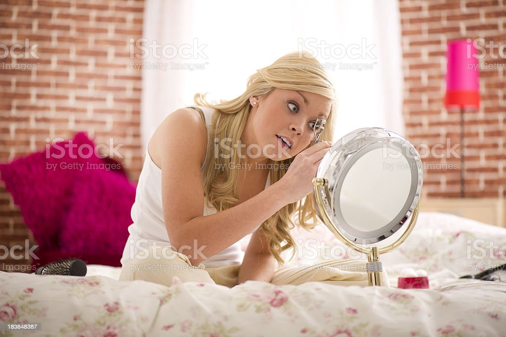 Young woman doing her eyelashes stock photo