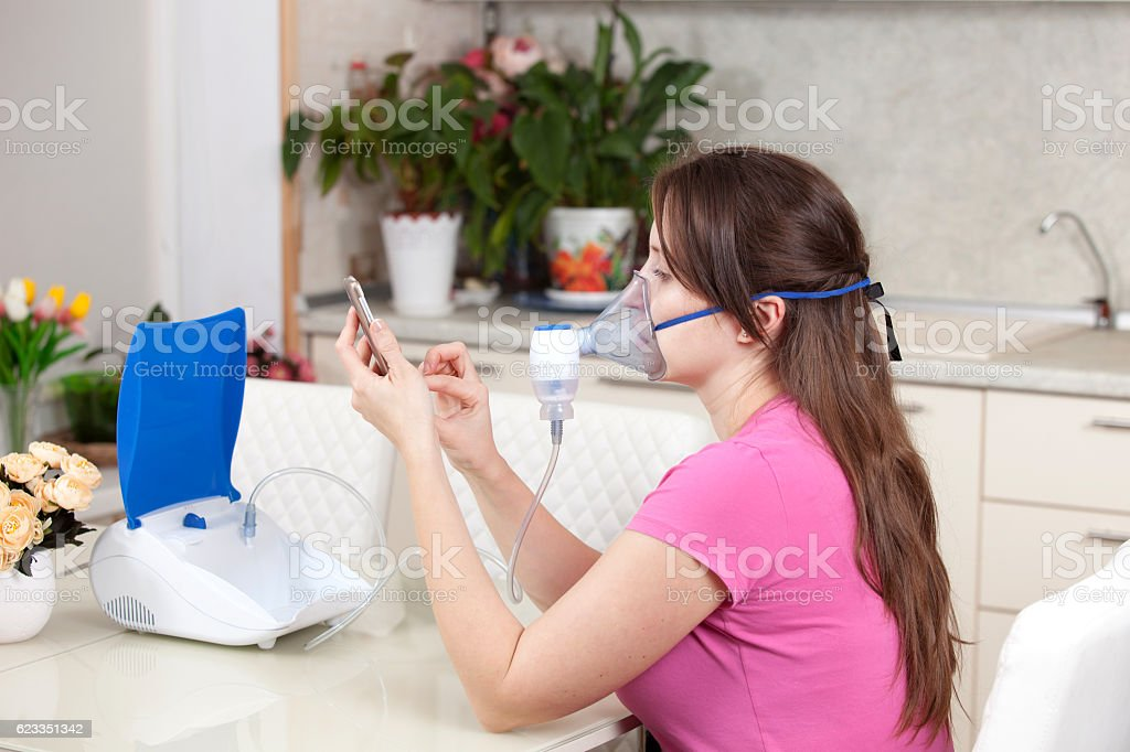 Young woman doing inhalation with a nebulizer at home stock photo