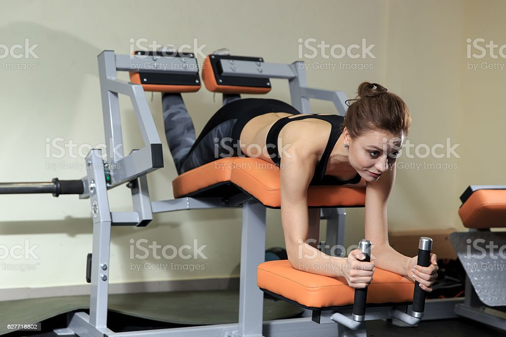 Young Woman Doing Leg With Machine In Gym stock photo