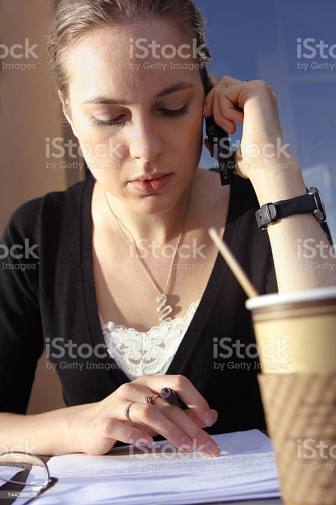 Young woman doing paperwork at cafe royalty-free stock photo