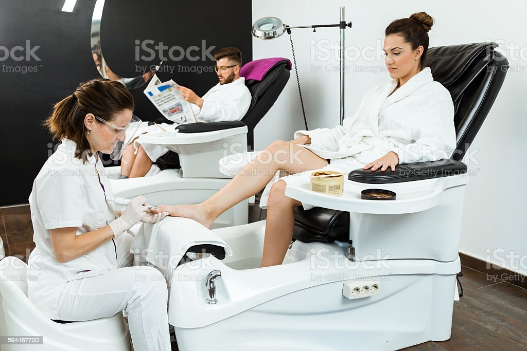 Young woman doing pedicure in salon. Beauty concept. stock photo