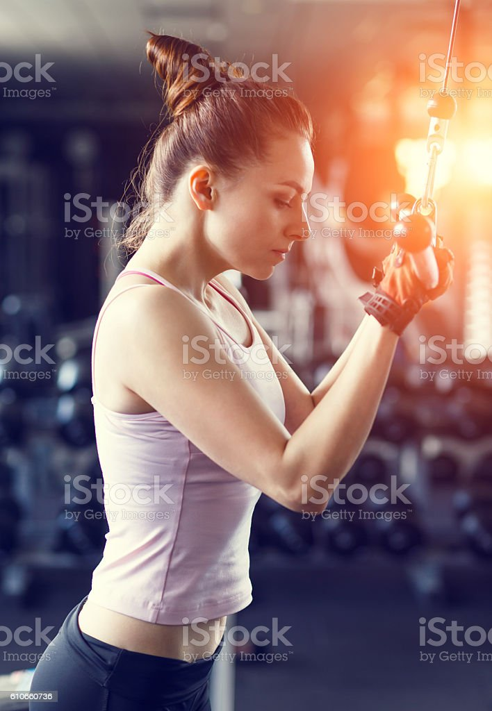 Young woman doing pushdown on cable machine in gym stock photo