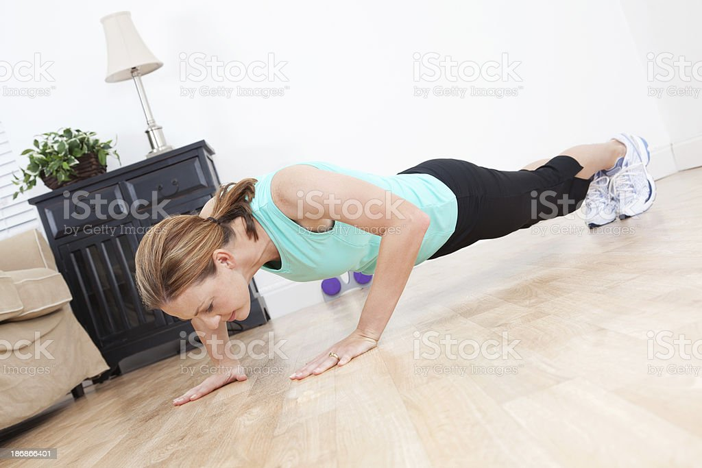 Young woman doing push-ups in her living room royalty-free stock photo
