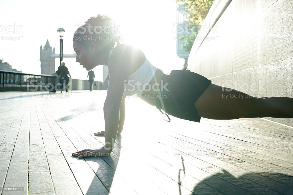 Young Woman Doing Pushups Outdoors In The Early Morning stock photo