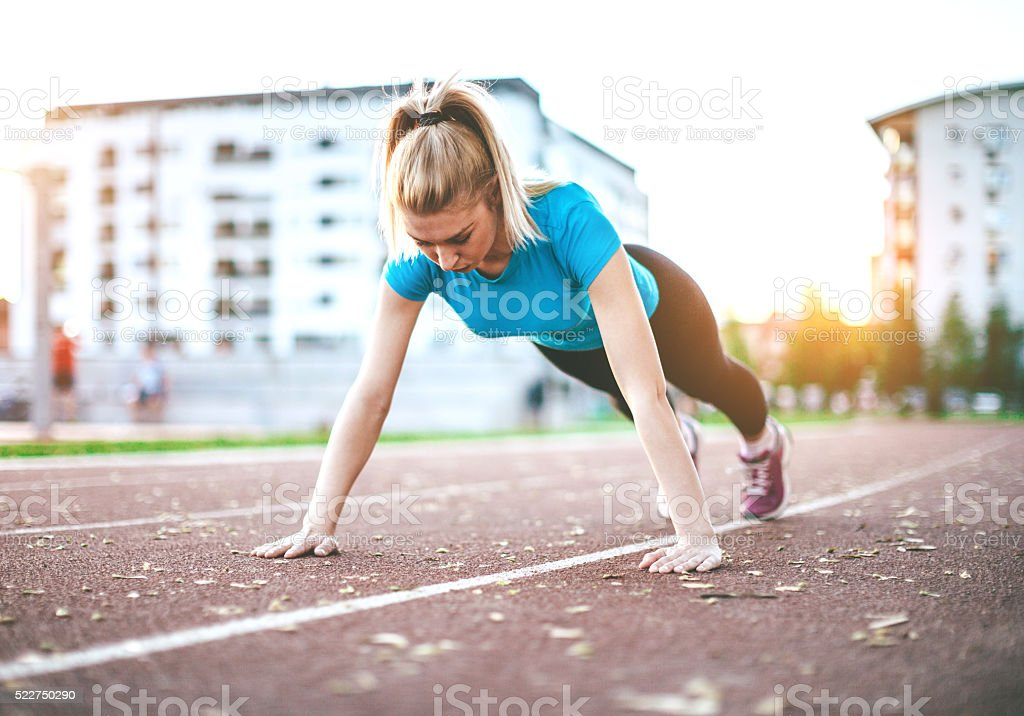 young woman doing push-ups stock photo