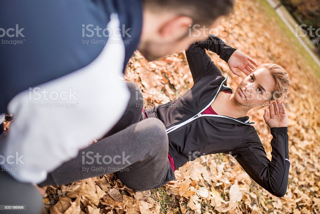 Young woman doing sit-ups with a help of her boyfriend. stock photo