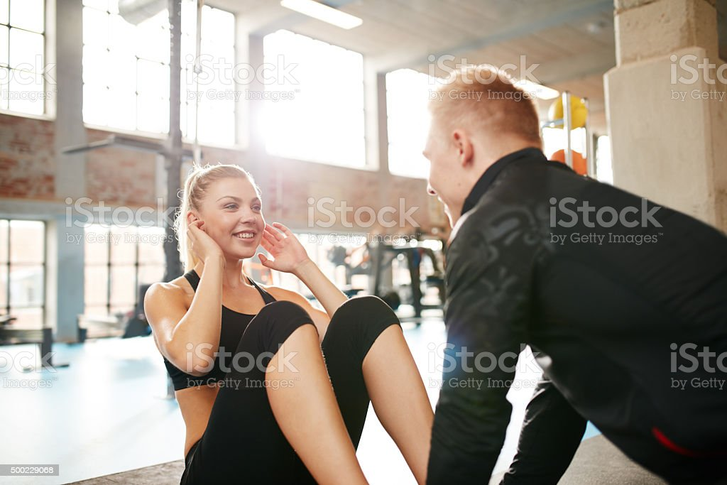 Young woman doing sit-ups with her personal trainer stock photo