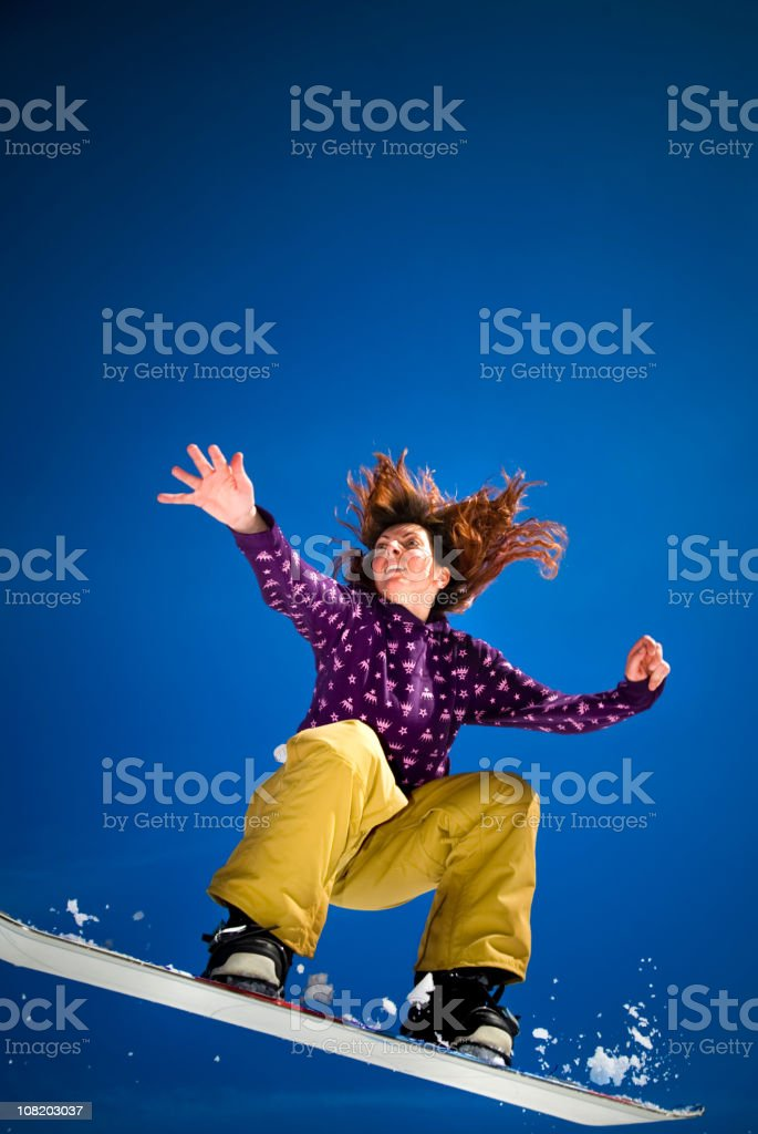 Young Woman Doing Snowboard Jump Against Clear Blue Sky royalty-free stock photo