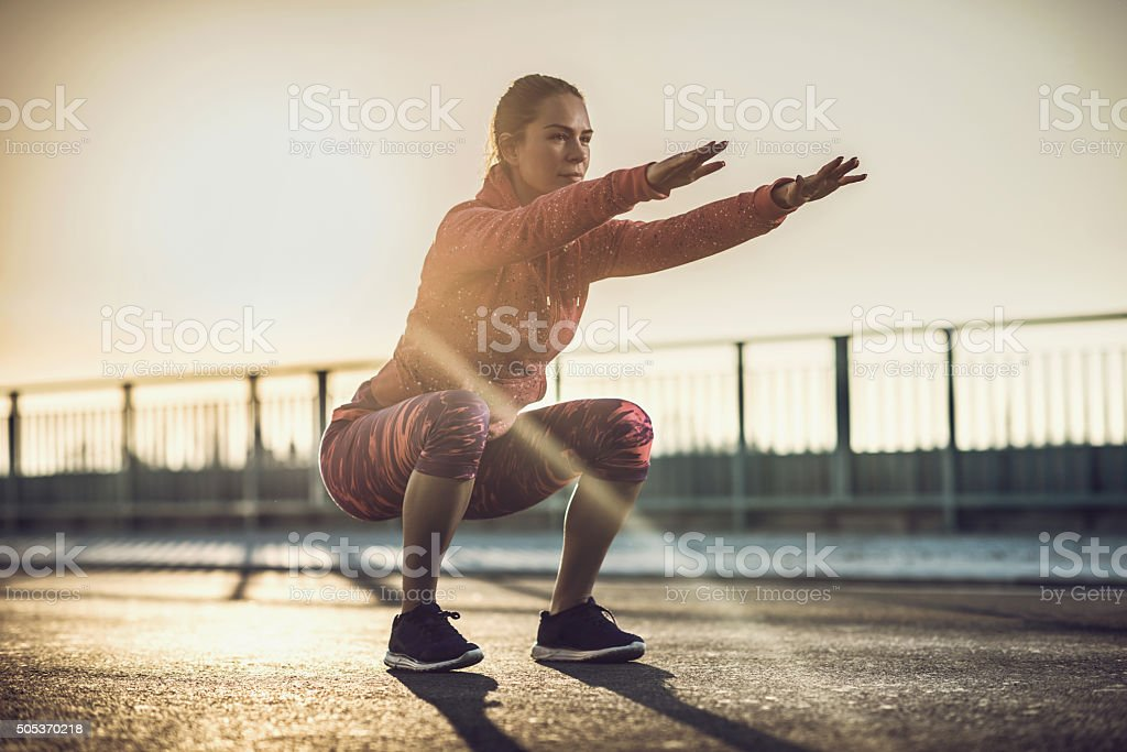 Young woman doing squats on a road at sunset. stock photo