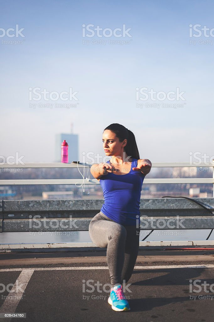 Young woman doing squats on a road royalty-free stock photo