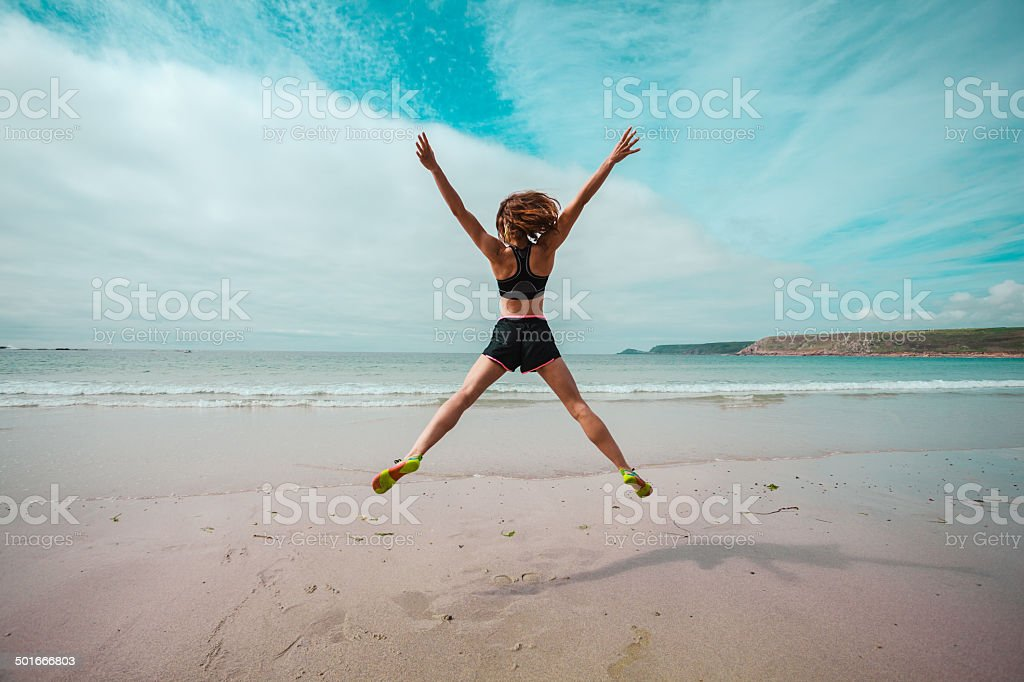 Young woman doing star jumps on the beach stock photo