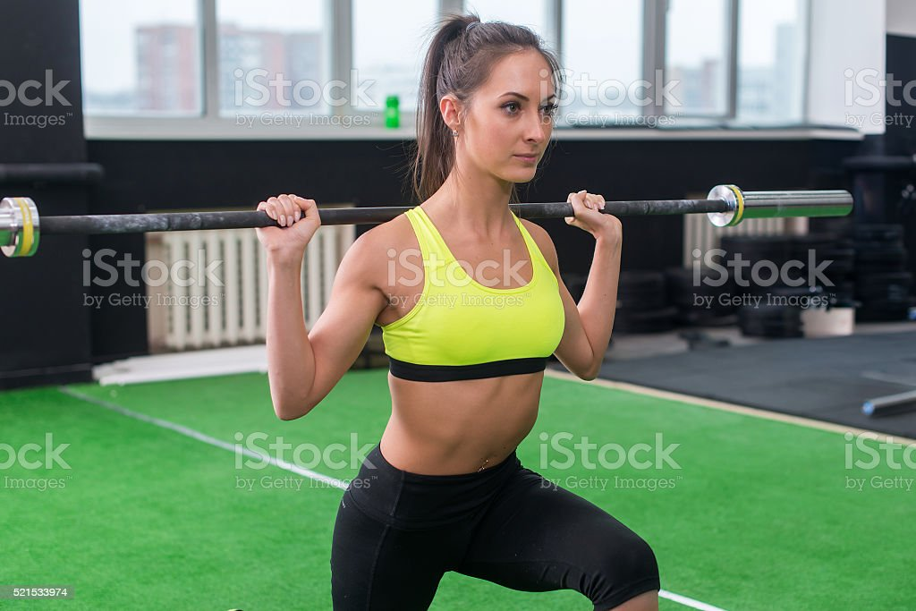 young woman doing weightlifting exercises, athletic female squatting with barbell stock photo