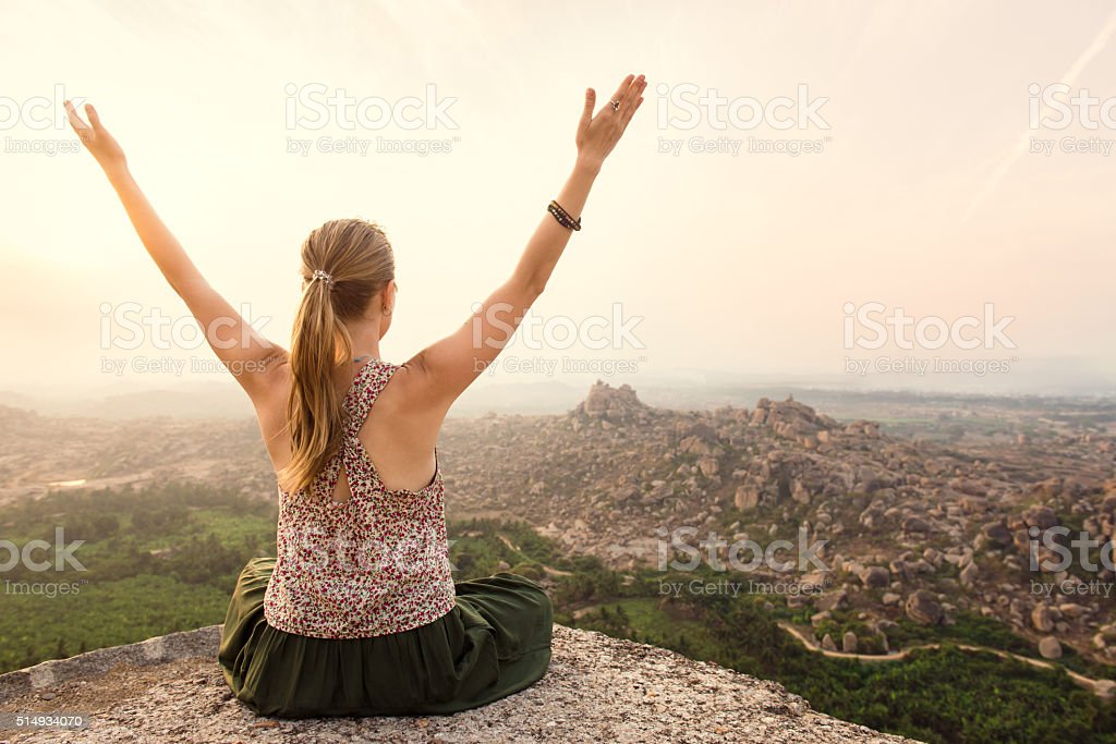 Young woman doing yoga at mountain cliff on sunrise stock photo
