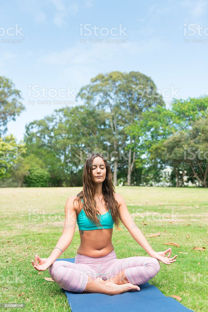 Young woman doing yoga at the park stock photo