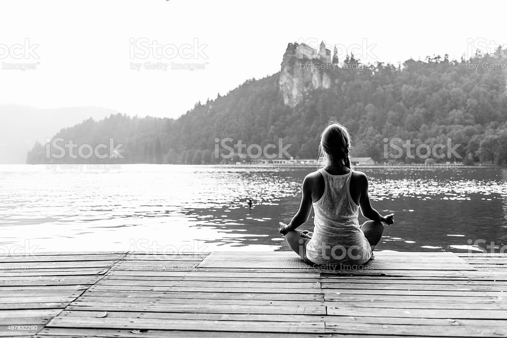 Young woman doing yoga by the lake, lotus position stock photo