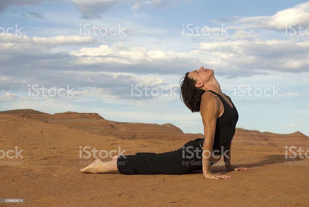 Young Woman Doing Yoga Cobra Pose on Utah Red Rocks royalty-free stock photo