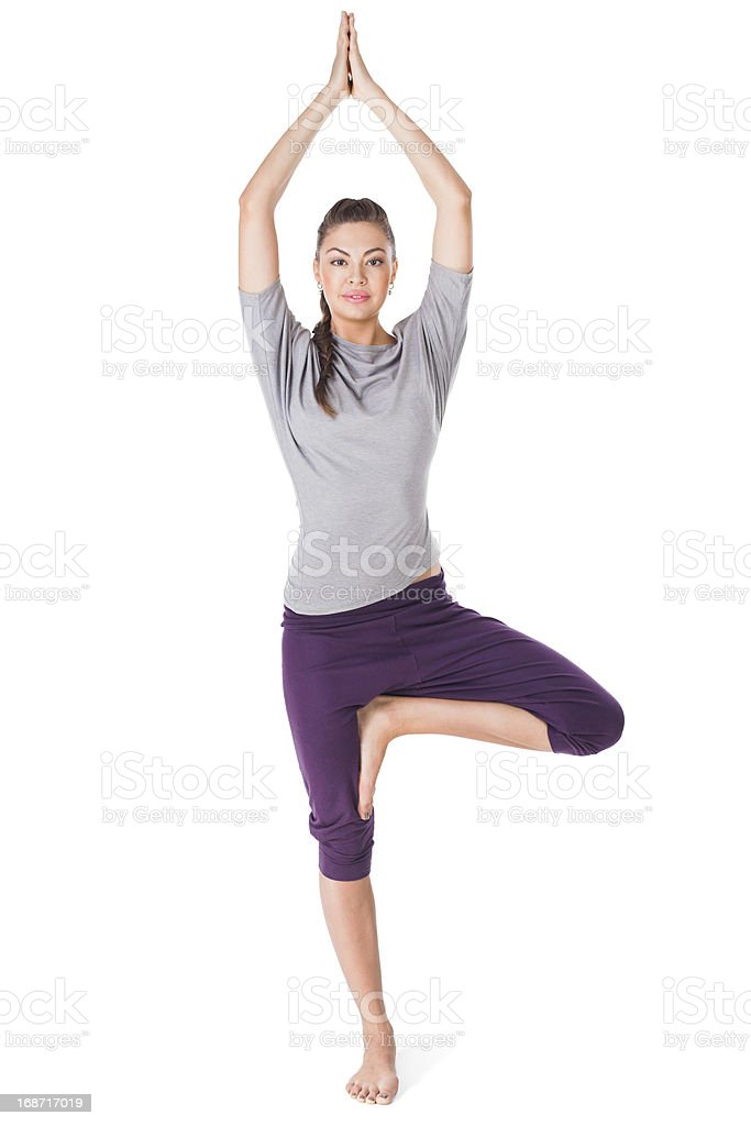 Young woman doing yoga exercise tree-pose isolated on white stock photo