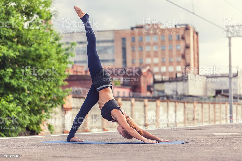 Young woman doing yoga exercises at sunset stock photo