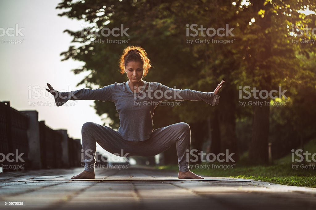 Young Woman Doing Yoga Exercises in Park stock photo