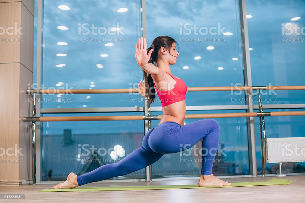 Young woman doing yoga exercises on mat at gym stock photo