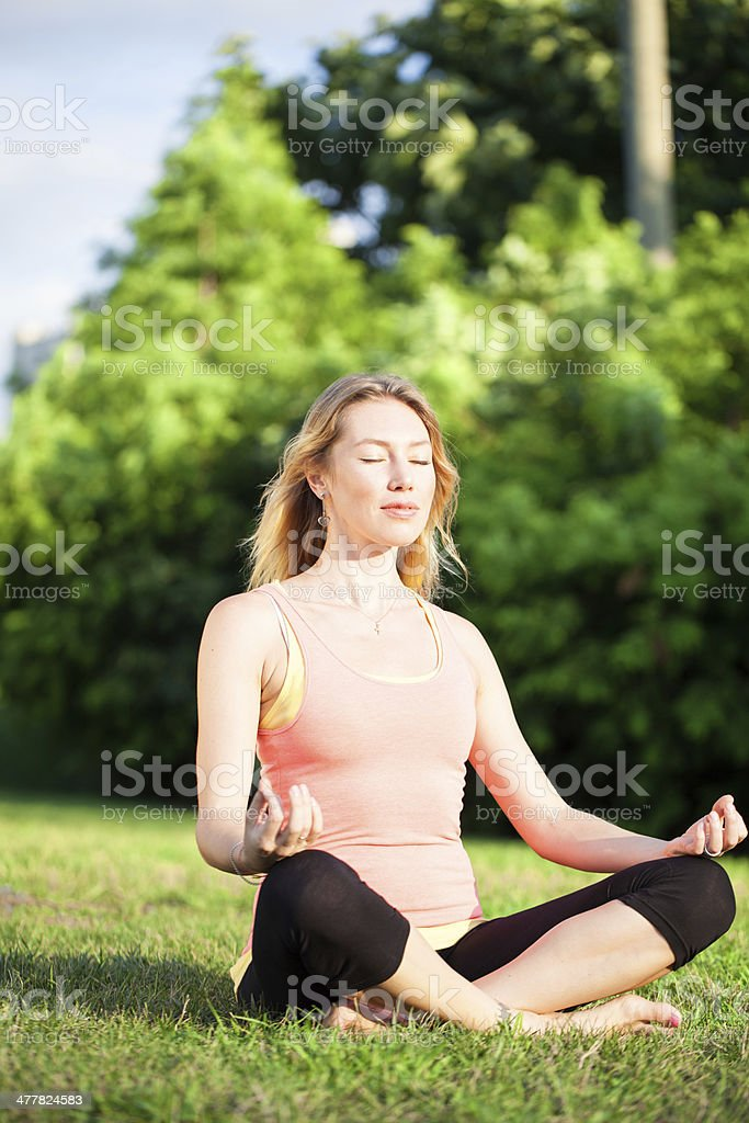Young woman doing yoga in park lotus position royalty-free stock photo