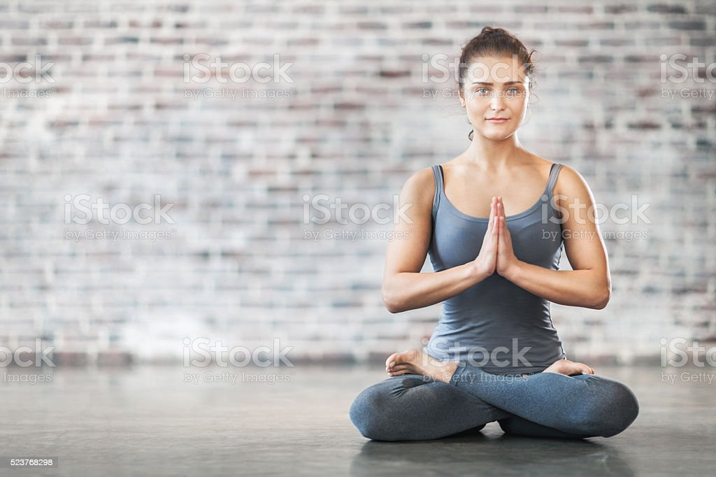 Young Woman Doing Yoga Meditation Exercise. Lotus Position stock photo