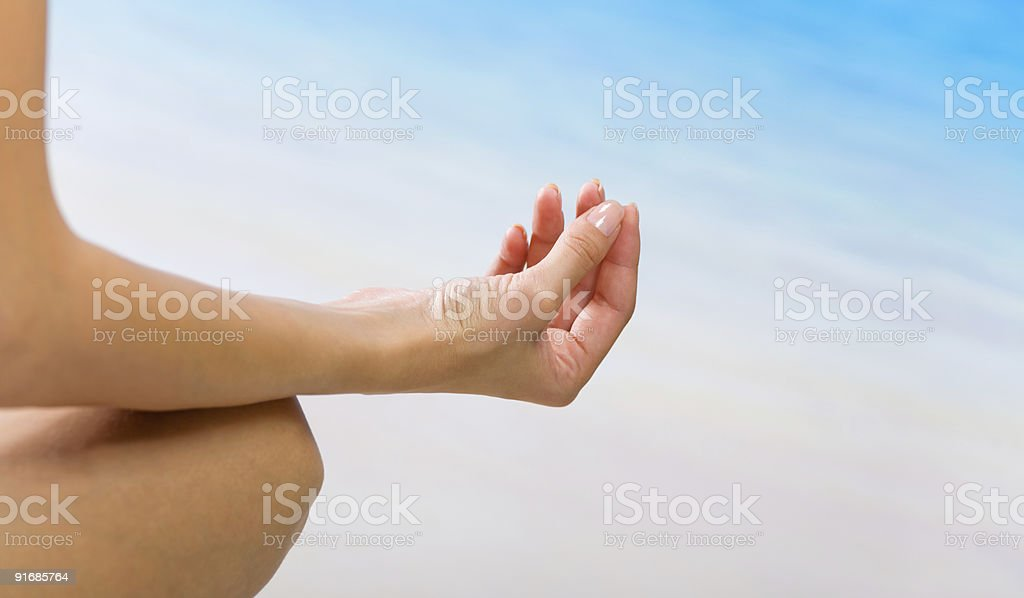 Young woman doing yoga moves or meditating on beach stock photo