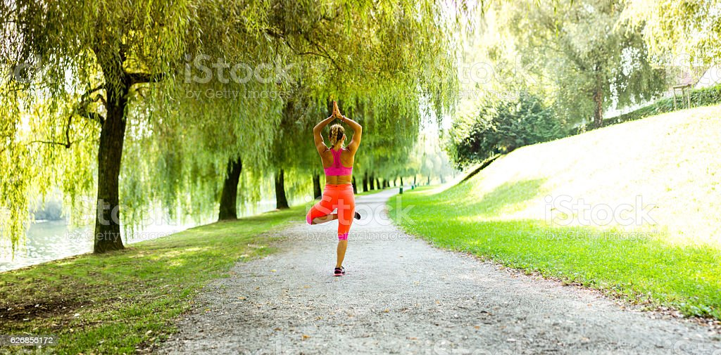 Young woman doing yoga mudras and poses in a park. stock photo