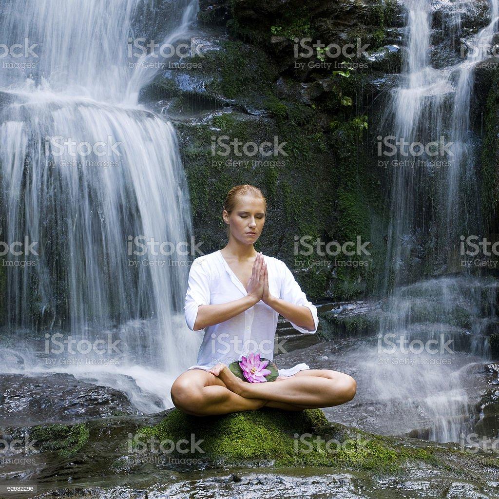 Young woman doing yoga near waterfalls royalty-free stock photo