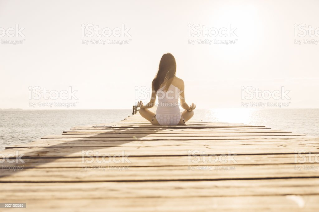 young woman doing yoga on pier stock photo