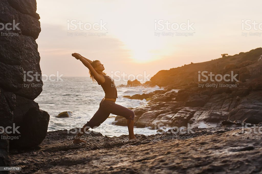young woman doing yoga on rock by sea royalty-free stock photo