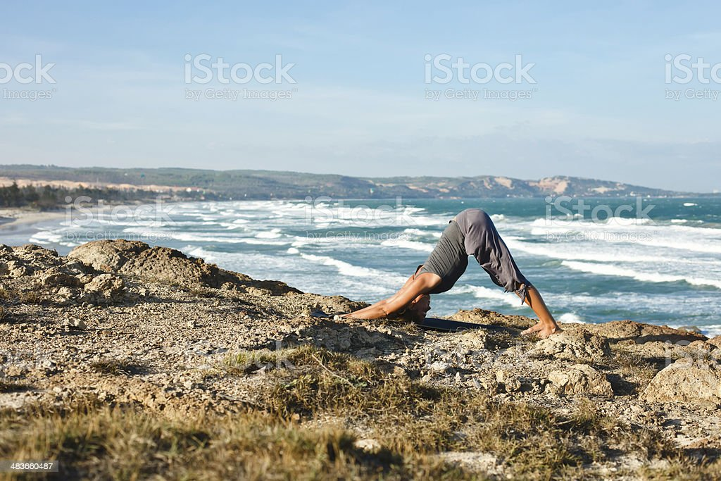 young woman doing yoga on the beach royalty-free stock photo