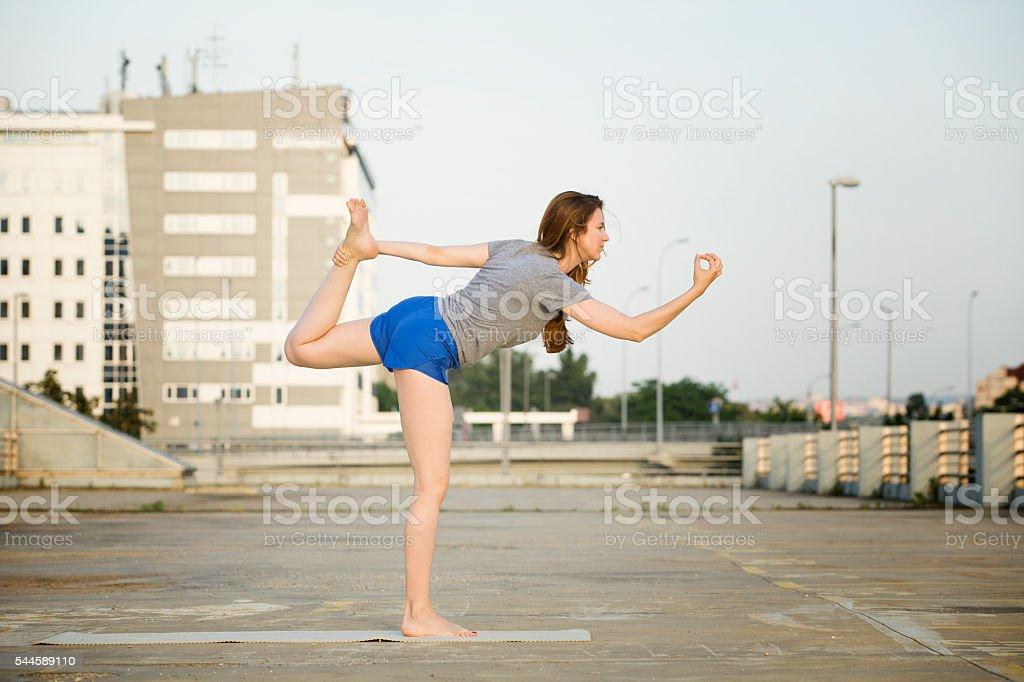 Young woman doing yoga outdoors in an urban neighbourhood stock photo