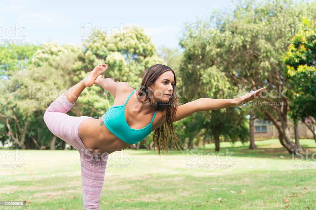 Young woman doing yoga outdoors stock photo