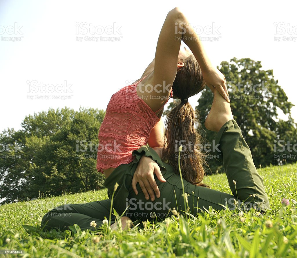 Young Woman Doing Yoga Stretch in Green Grass Outdoors royalty-free stock photo